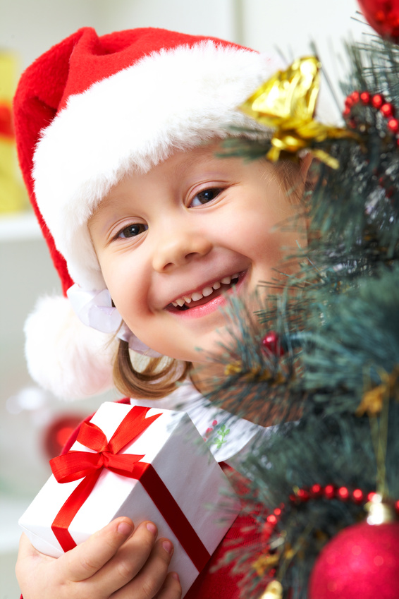 Portrait of little cute girl with  present  near Christmas tree